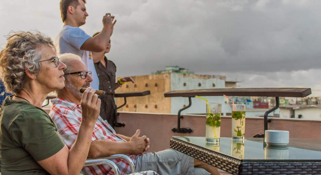 Tourists watching the city sunset while smoking a Cuban Cigar